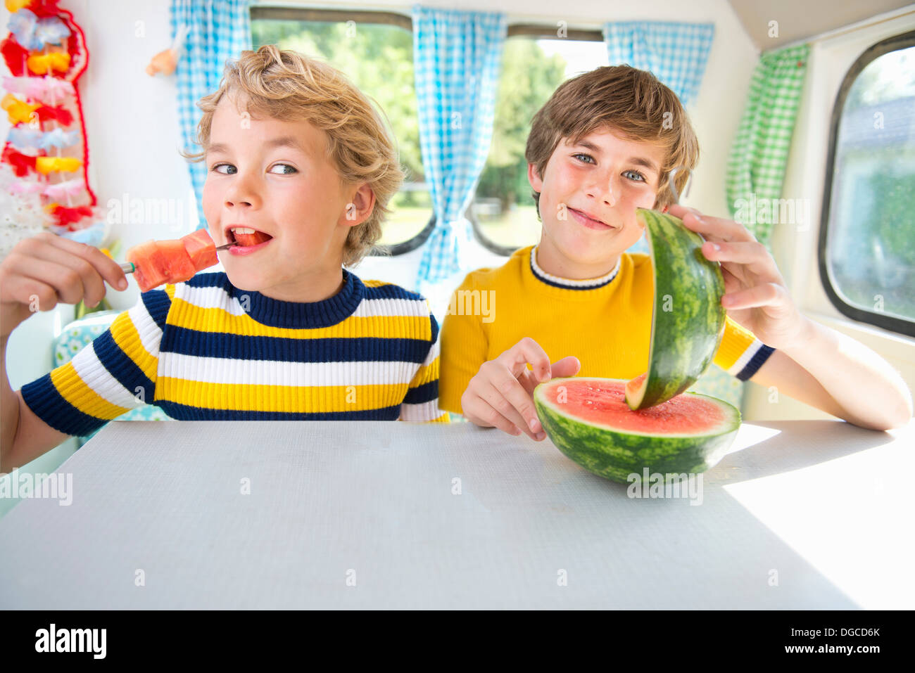 Ragazzi mangiare anguria in caravan, ritratto Immagini Stock