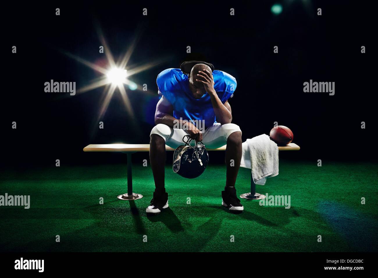 Ritratto di giocatore di football americano con testa in mano Foto Stock