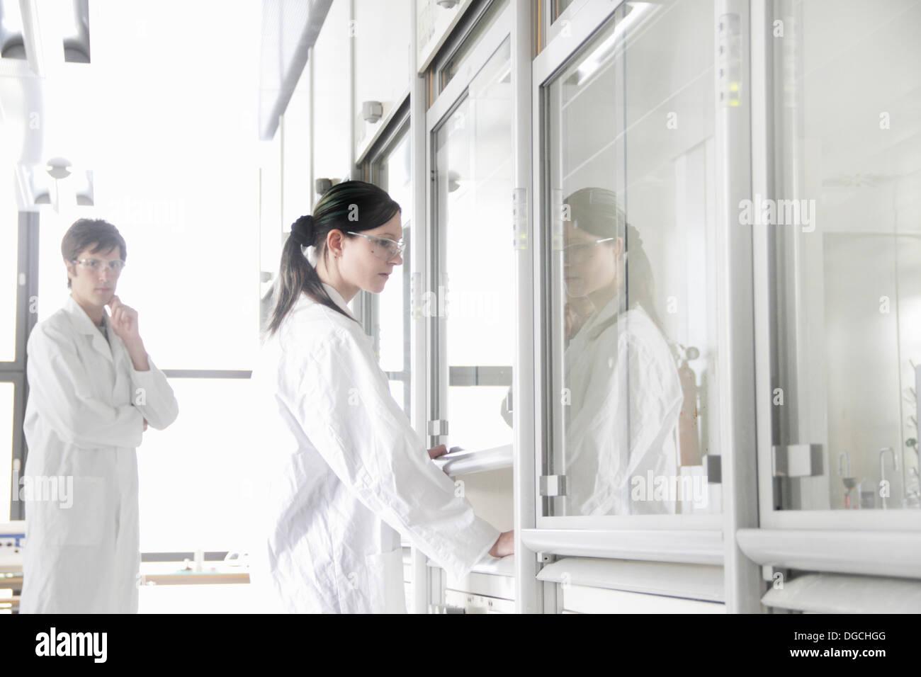 Studenti di chimica dalla cappa chimica in laboratorio Immagini Stock