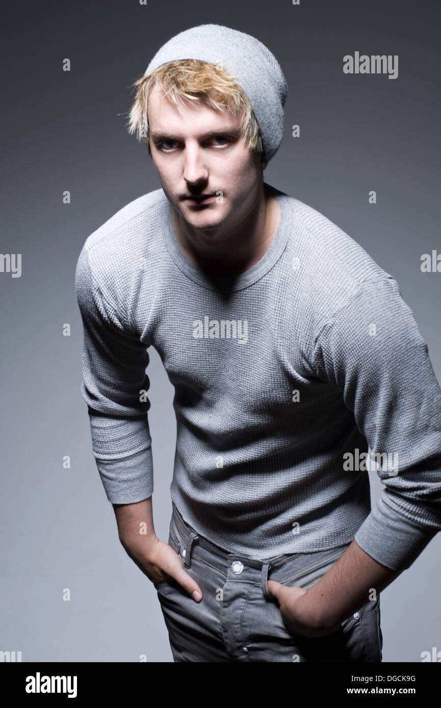 Giovane uomo in grigio felpa con le mani nelle tasche, ritratto Immagini Stock