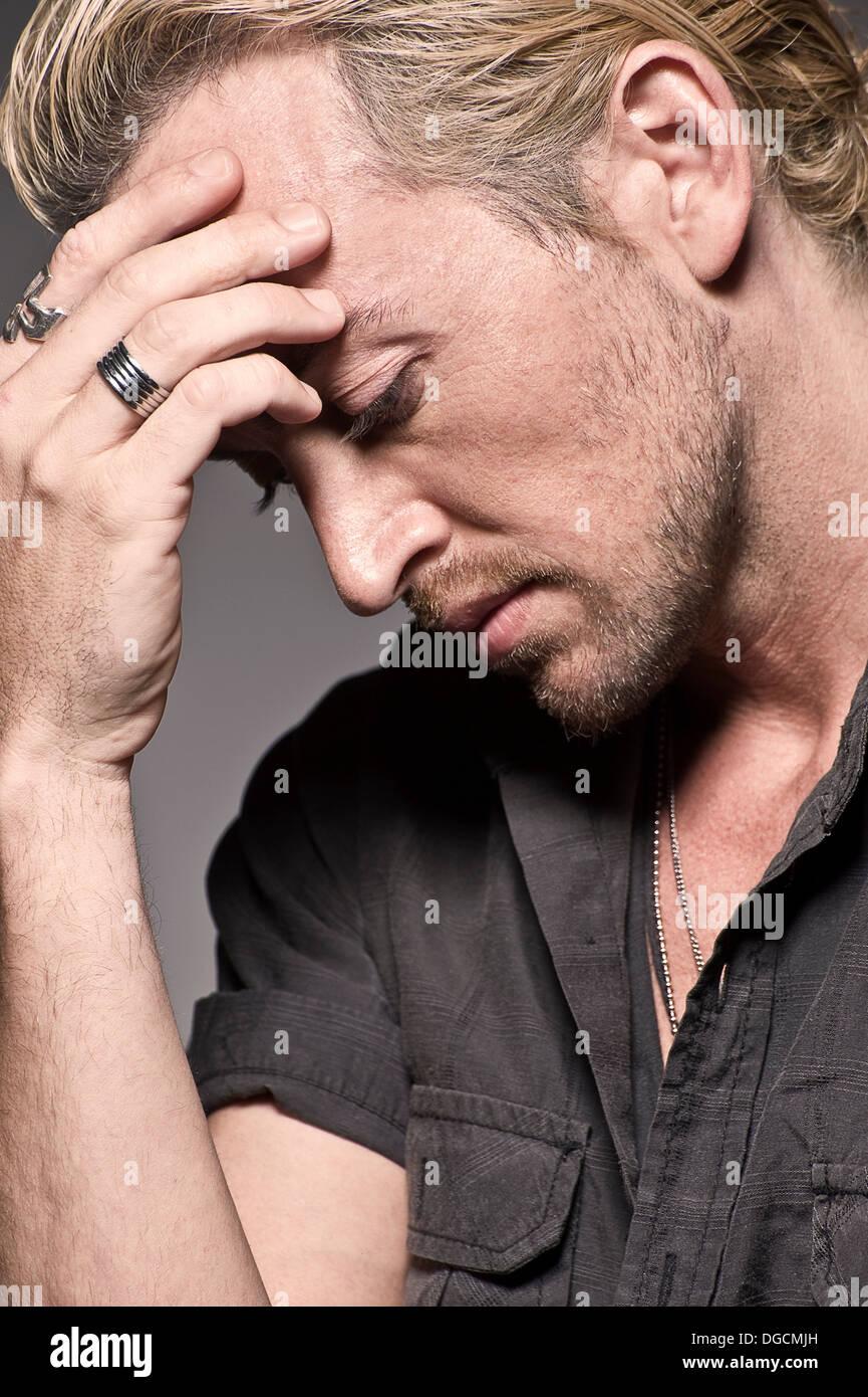 Giovane uomo con testa in mani, studio shot Immagini Stock