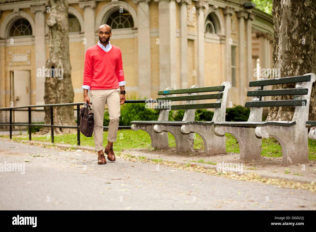 Giovane uomo che porta nella valigetta attraverso park Immagini Stock
