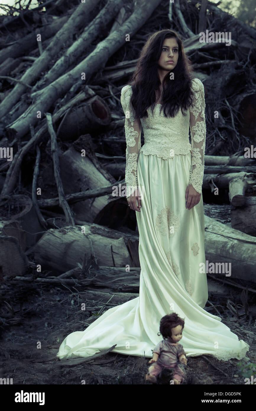 La donna in un antico edificio di abito da sposa con tagliare gli alberi e creepy doll Immagini Stock