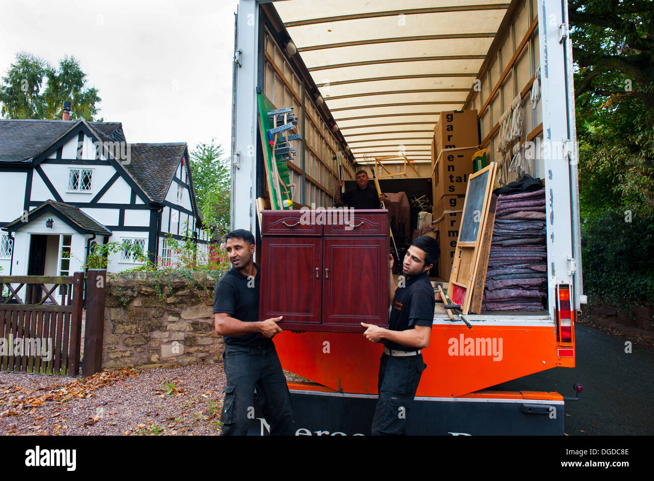 Distacco gli uomini che trasportano mobili in un bianco e nero Cottage, Shropshire, Inghilterra Immagini Stock