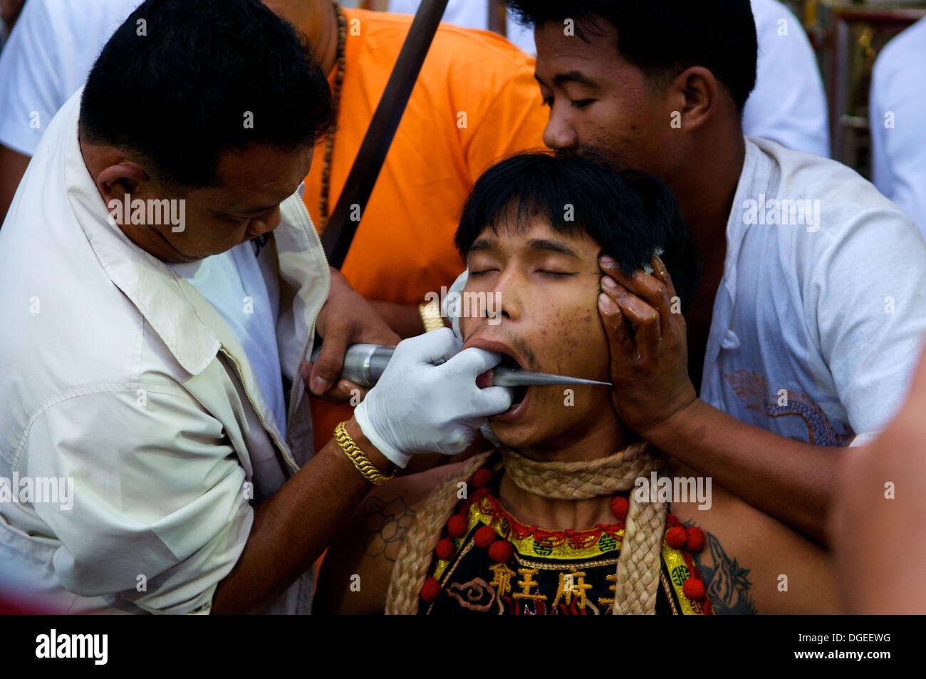 Ma-Thong (media di spirito) getting guancia trafitto con piercing gage durante il Phuket Festival vegetariano, città di Phuket, Tailandia Immagini Stock