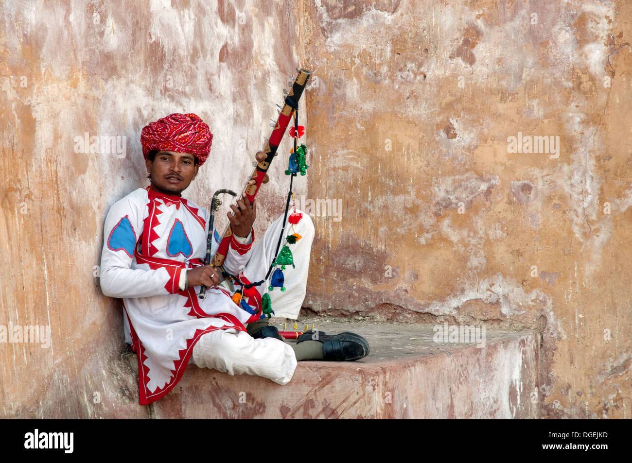 Uomo di Rajasthani che posano con strumento tradizionale all'interno Amer Fort, a Jaipur, India Immagini Stock