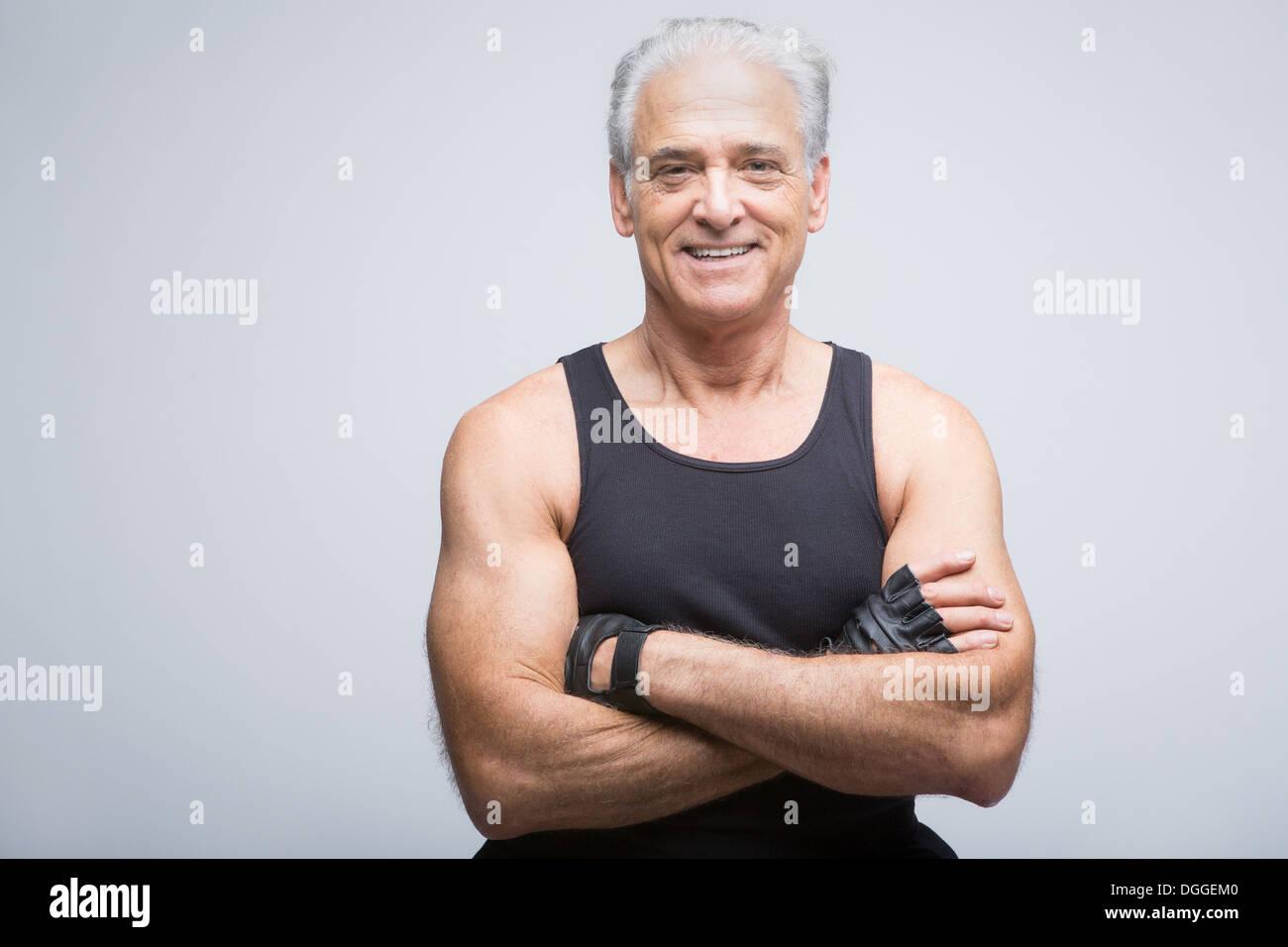 Senior uomo in abbigliamento sportivo con le braccia incrociate, ritratto Foto Stock
