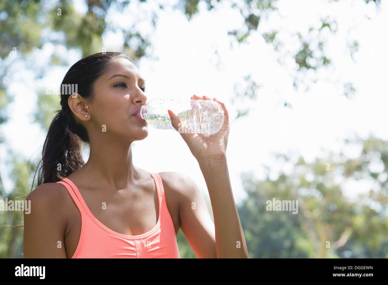 Giovane donna di bere dalla bottiglia di acqua Immagini Stock