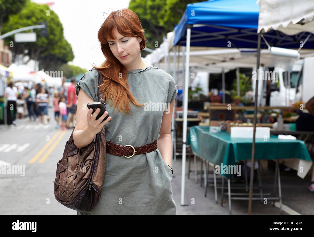 Metà donna adulta guardando al telefono cellulare in città Immagini Stock