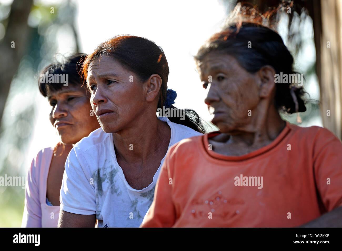 Tre donne con preoccupazione le espressioni del viso, in una comunità di Indiani Guarani, Jaguary, Caaguazú Reparto, Paraguay Immagini Stock