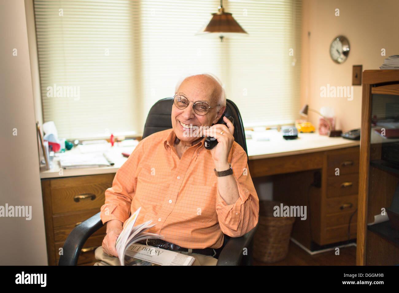 Senior l uomo con il telefono in home office, sorridente Immagini Stock