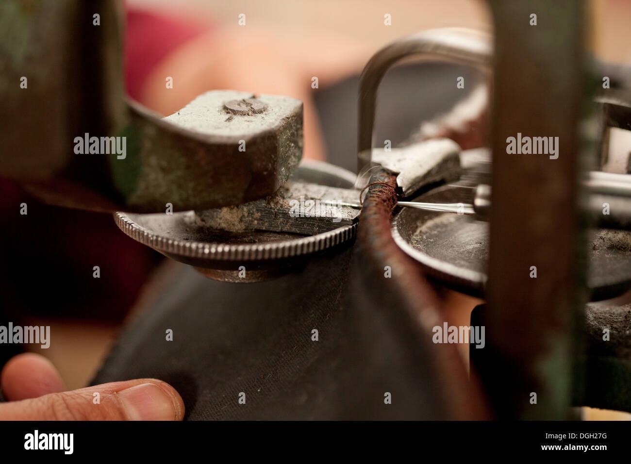 Close up della persona che utilizza la macchina per lavorare le pelli Immagini Stock