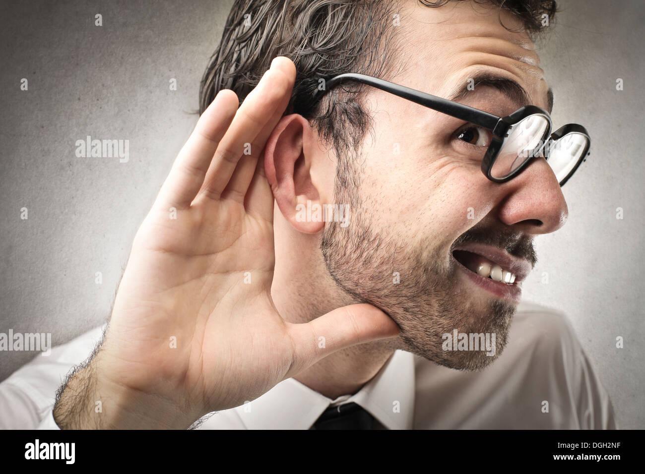 Lavoratore di ufficio con gli occhiali non riesce a sentire qualcuno Immagini Stock