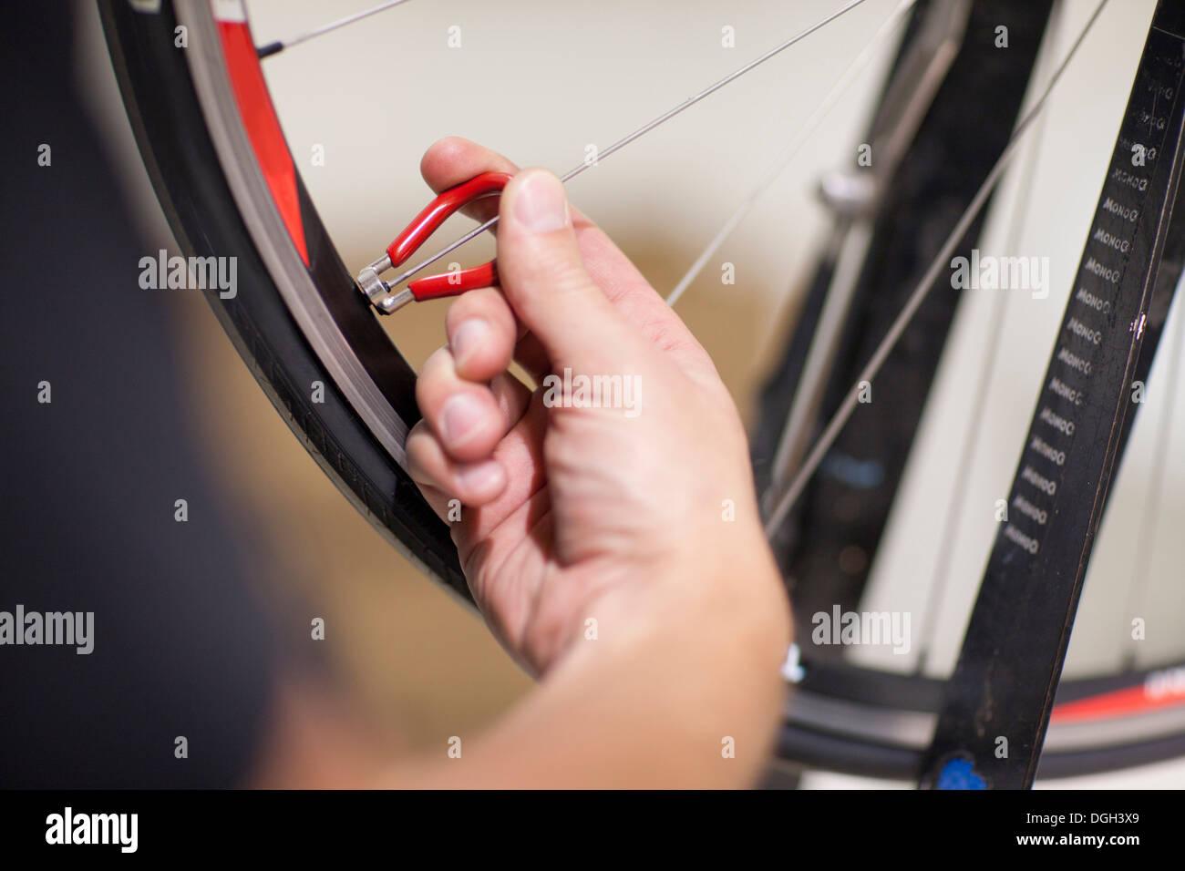Close up della persona che usa il parlato chiave sulla ruota di bicicletta Immagini Stock