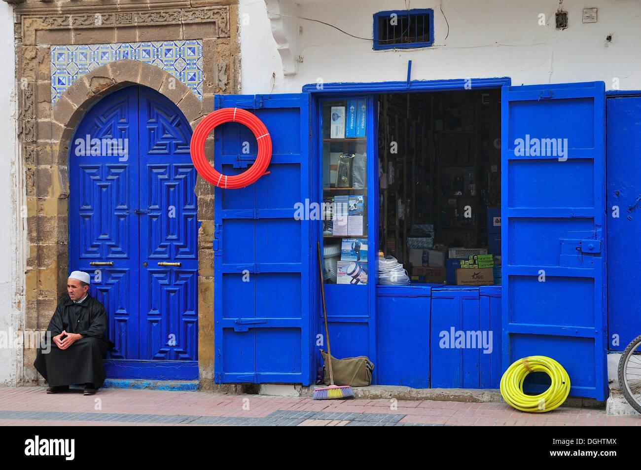 Uomo seduto di fronte a una porta blu accanto a un negozio di ferramenta, Essaouira, Marocco, Africa Immagini Stock