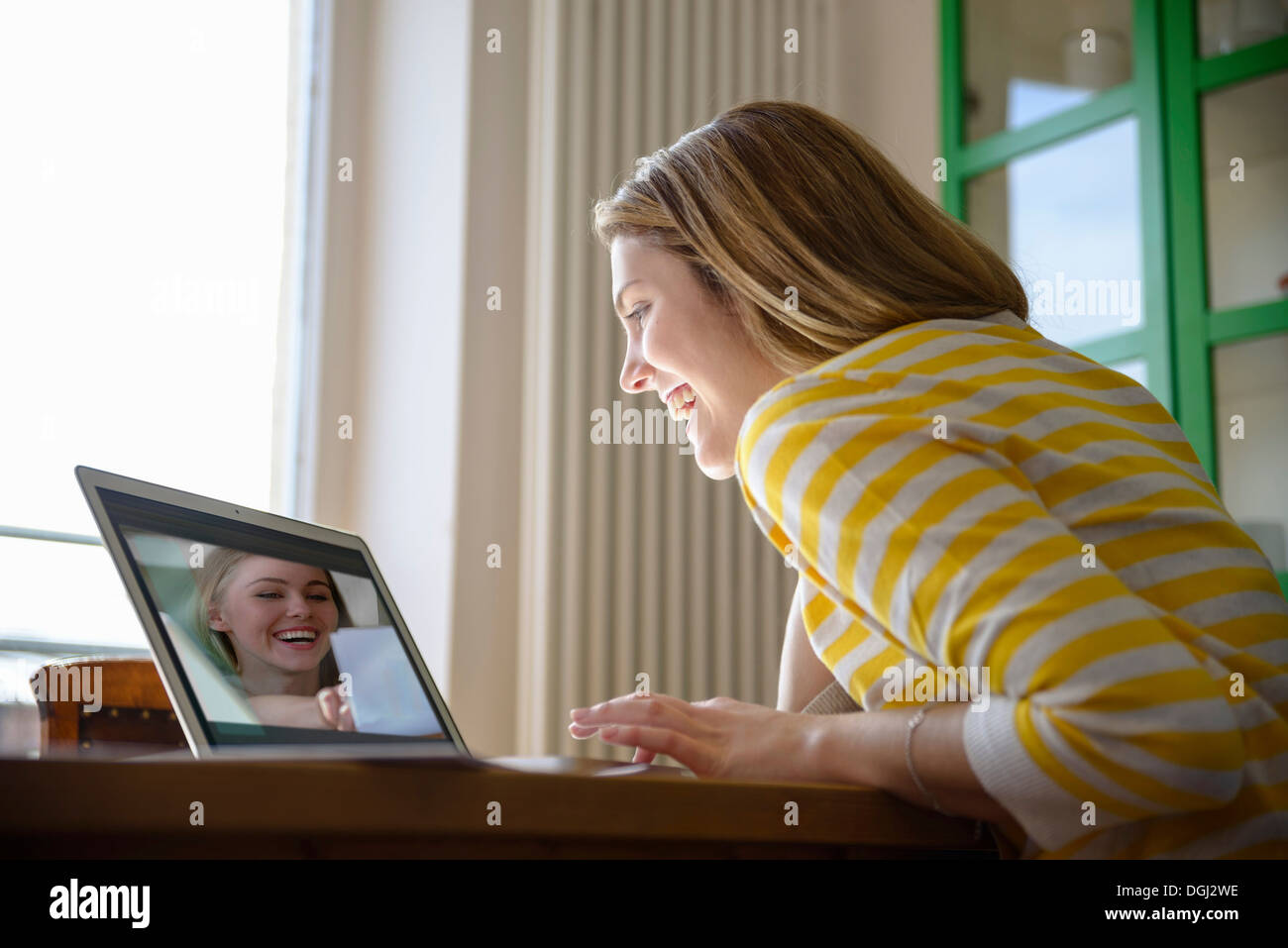 Giovane donna sulla chiamata video con un amico Immagini Stock