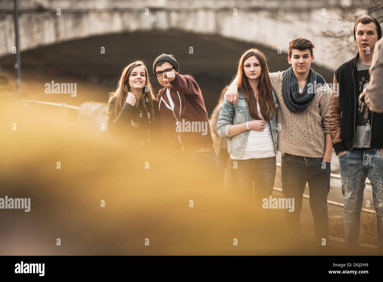 Cinque adolescenti all'aperto, ragazzo puntando alla fotocamera Foto Stock