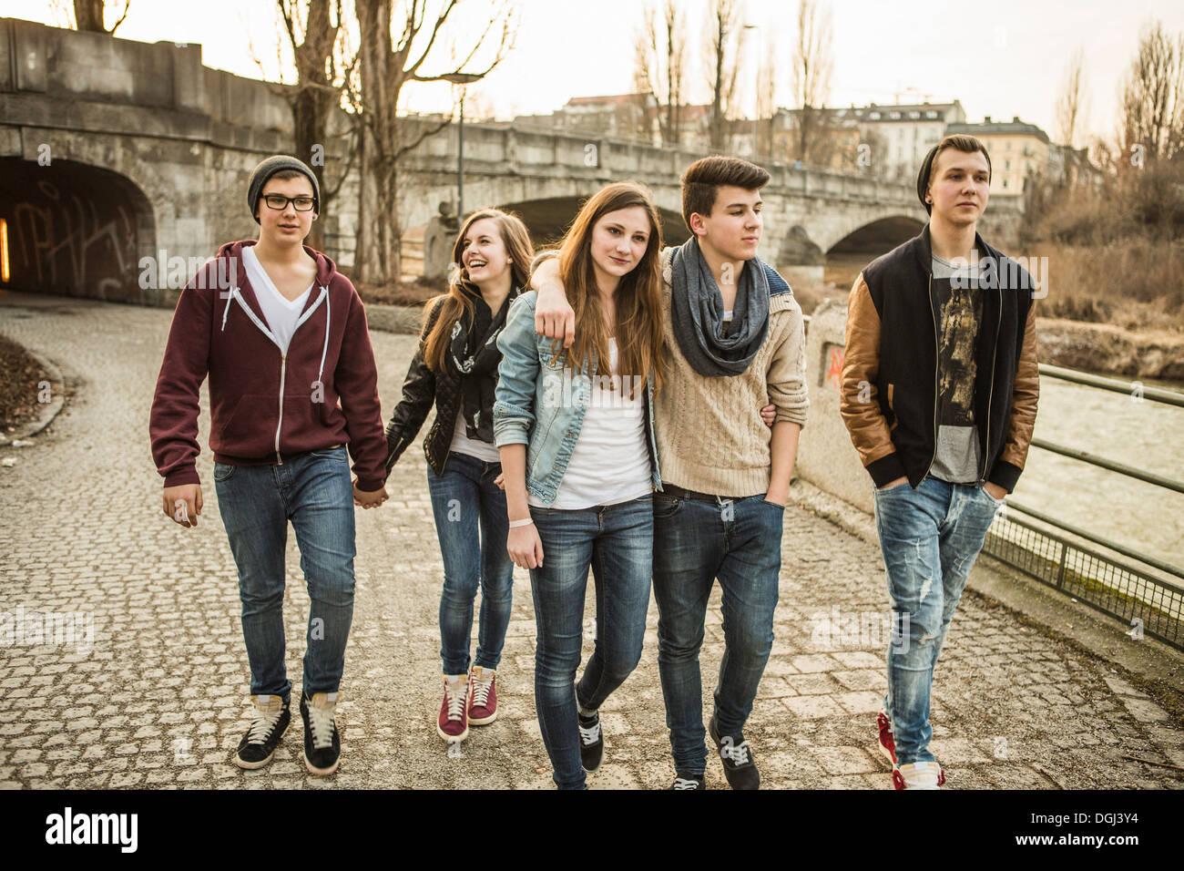 Cinque adolescenti camminare insieme accanto al fiume Immagini Stock