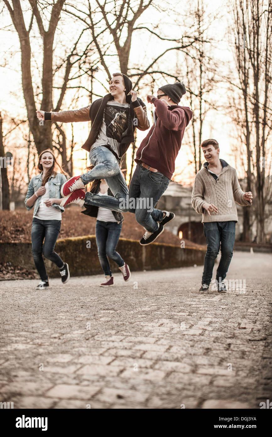 Cinque adolescenti ingannare intorno, saltando in posizione di parcheggio Immagini Stock
