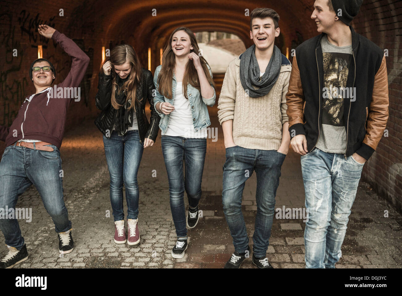 Cinque adolescenti a piedi attraverso il tunnel ridendo e scherzando Immagini Stock