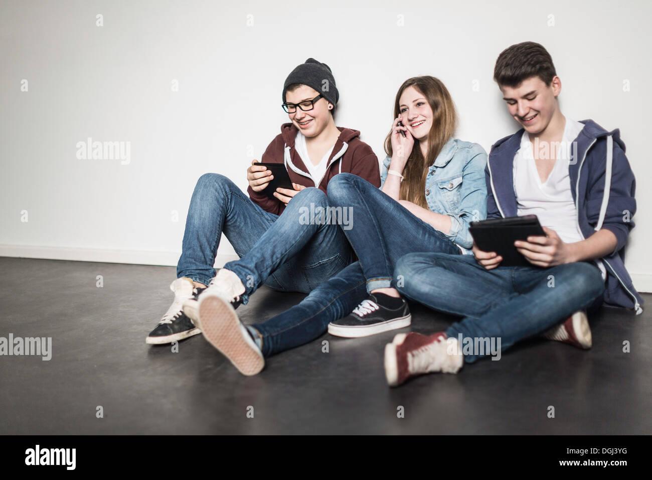 Tre adolescenti seduti sul pavimento usando la tecnologia Immagini Stock