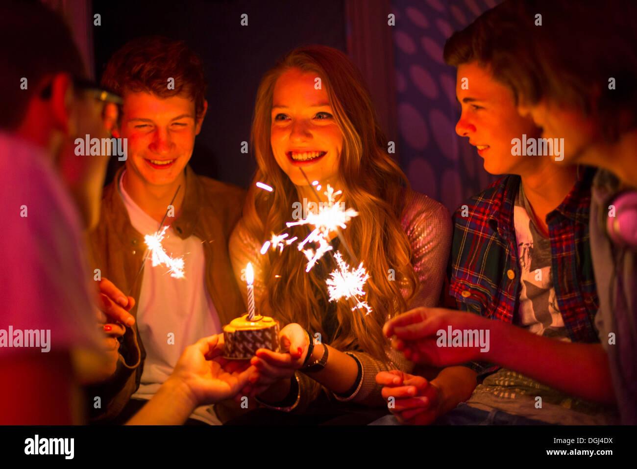 Gruppo di adolescenti seduti intorno a torta di compleanno con botti Immagini Stock