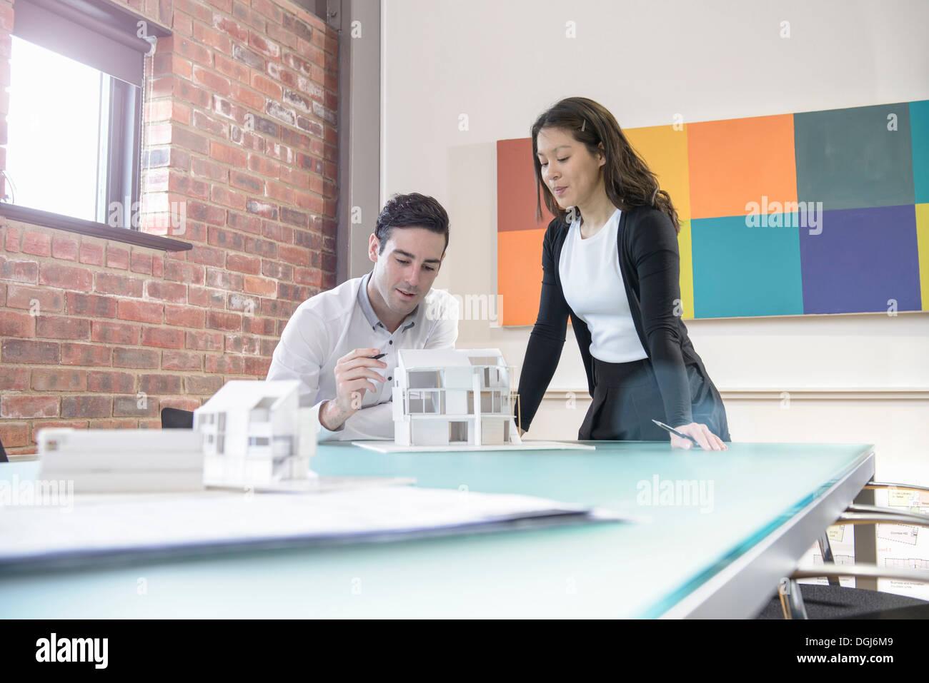 Gli architetti che lavorano insieme sul modello di edificio in ufficio Foto Stock