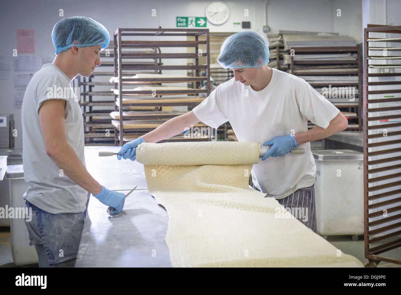 I panettieri in abbigliamento protettivo la preparazione di lunghezza di pasta Immagini Stock