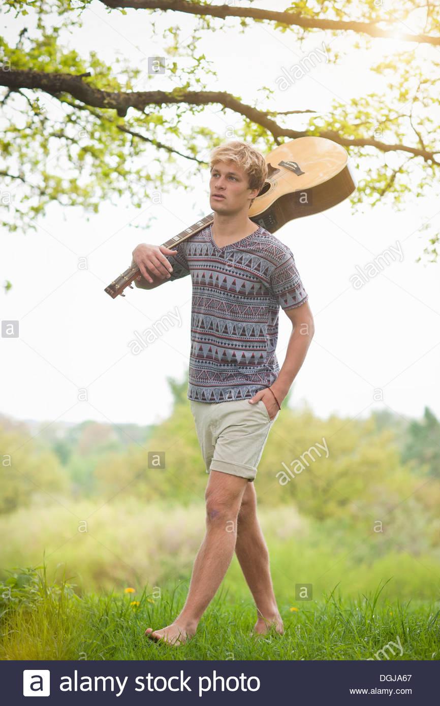 Giovane uomo a camminare attraverso il campo con la chitarra Foto Stock