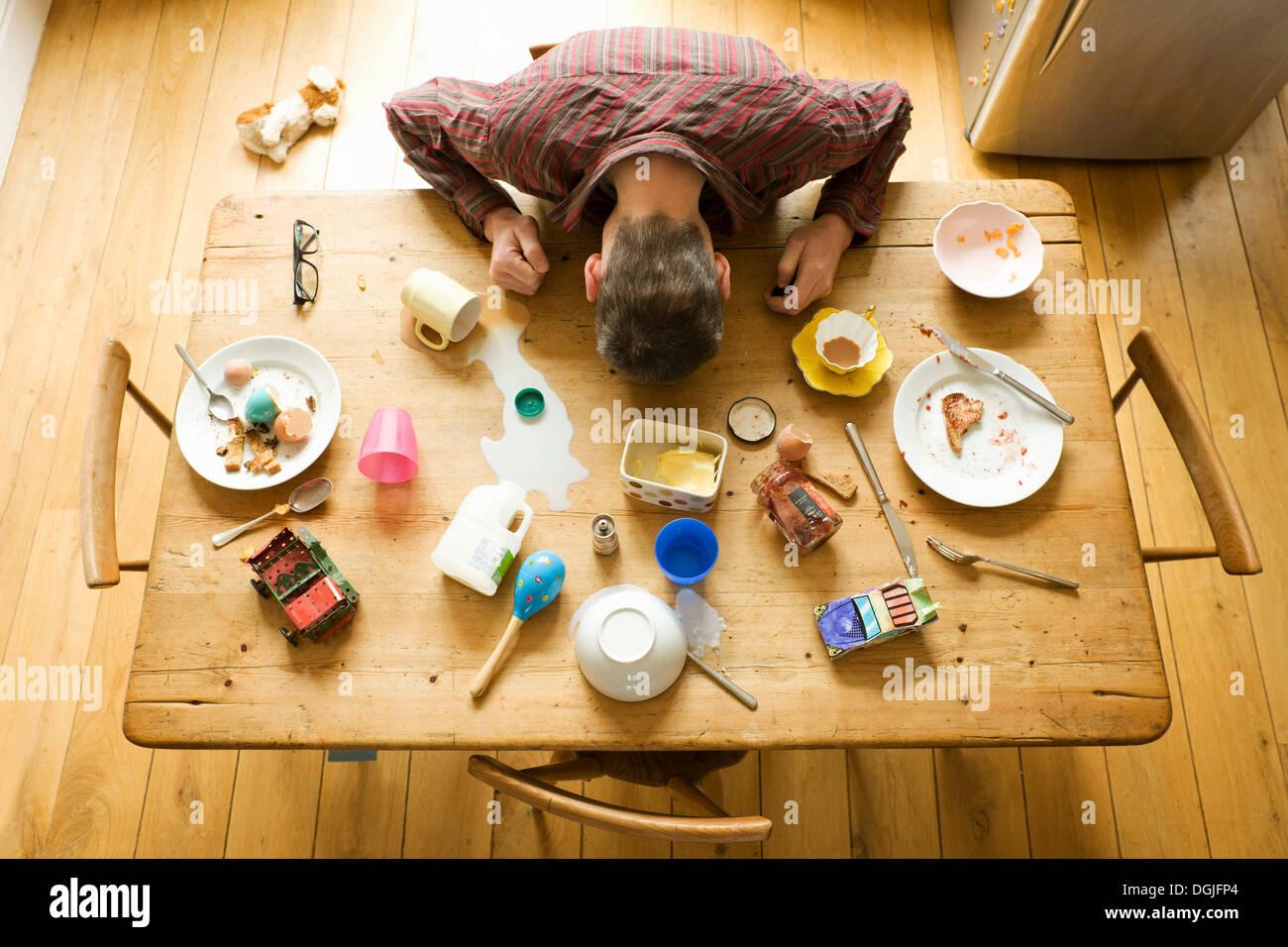 Vista aerea del tavolo per la colazione con uomo maturo tra piastre disordinati Immagini Stock