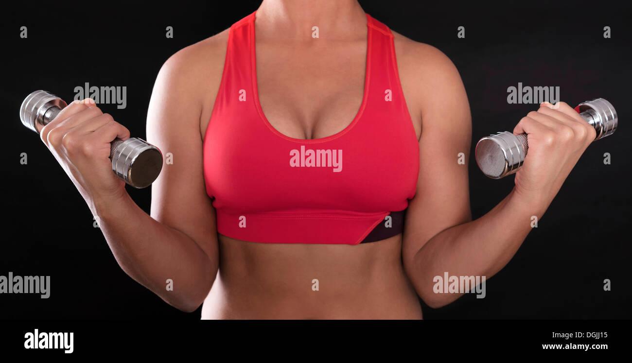 Giovane donna di corpo superiore che indossa un rosso reggiseno sportivo mentre si fa fitness training con manubri cromati Immagini Stock