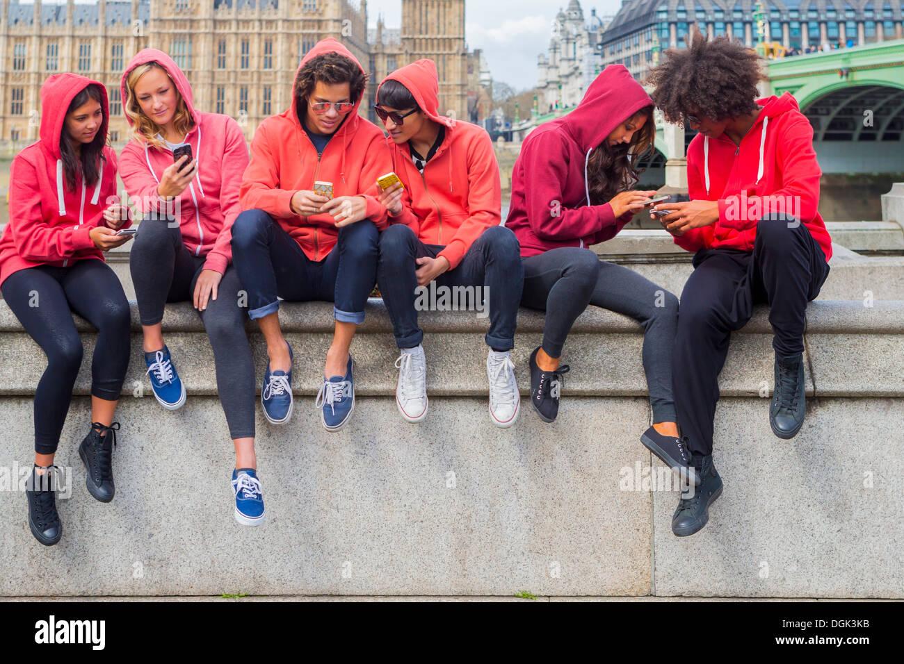 Piccolo gruppo di giovani la condivisione di informazioni mobili Immagini Stock