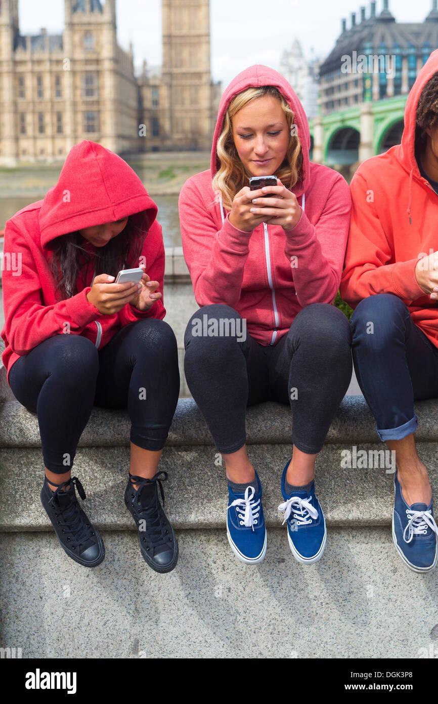 Tre giovani guardando i telefoni cellulari Immagini Stock