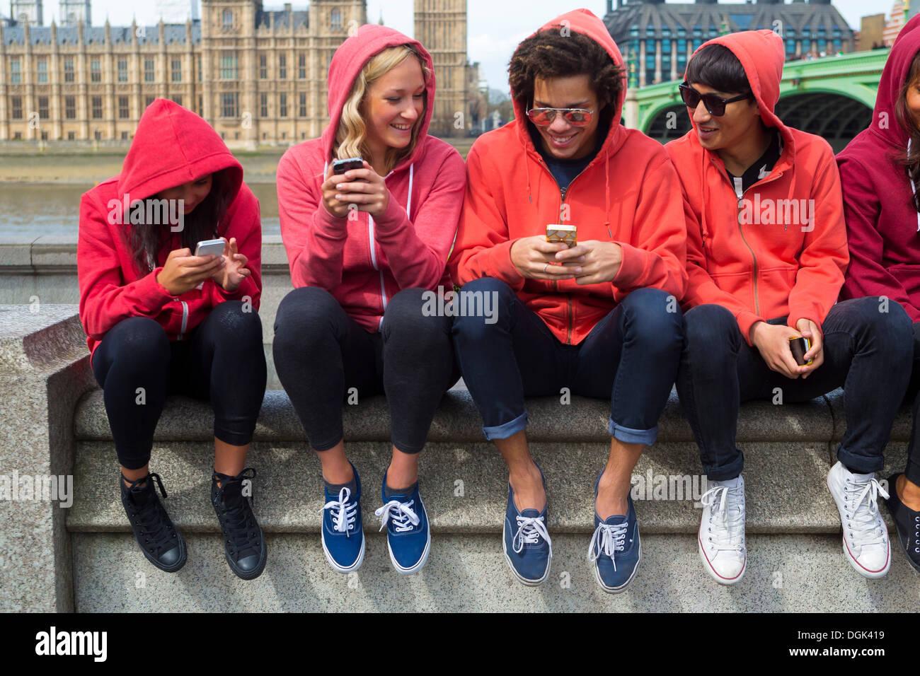 Un gruppo di giovani alla ricerca al telefono cellulare Immagini Stock