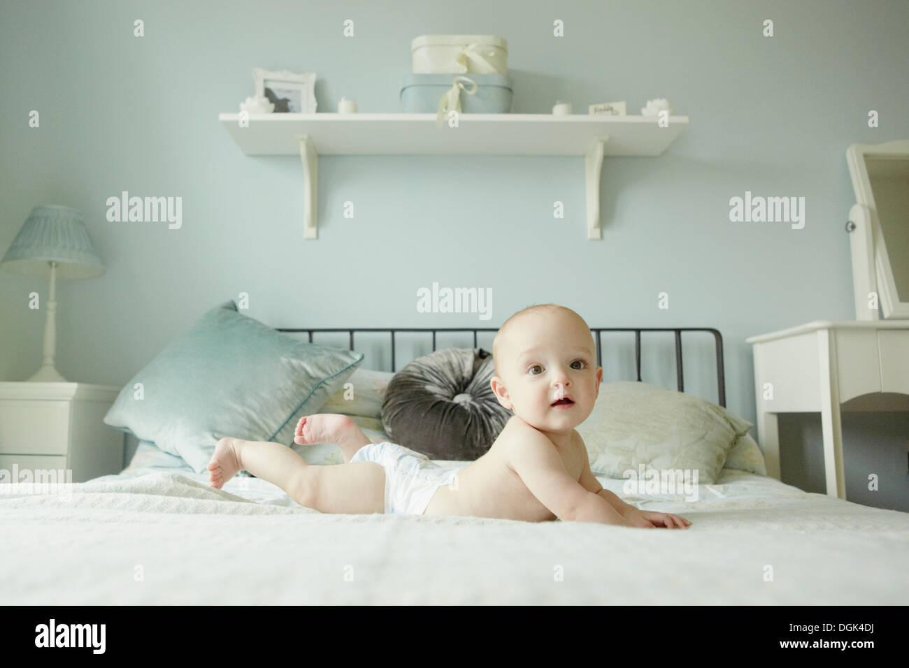 Bambino giacente sulla parte anteriore sul letto Immagini Stock