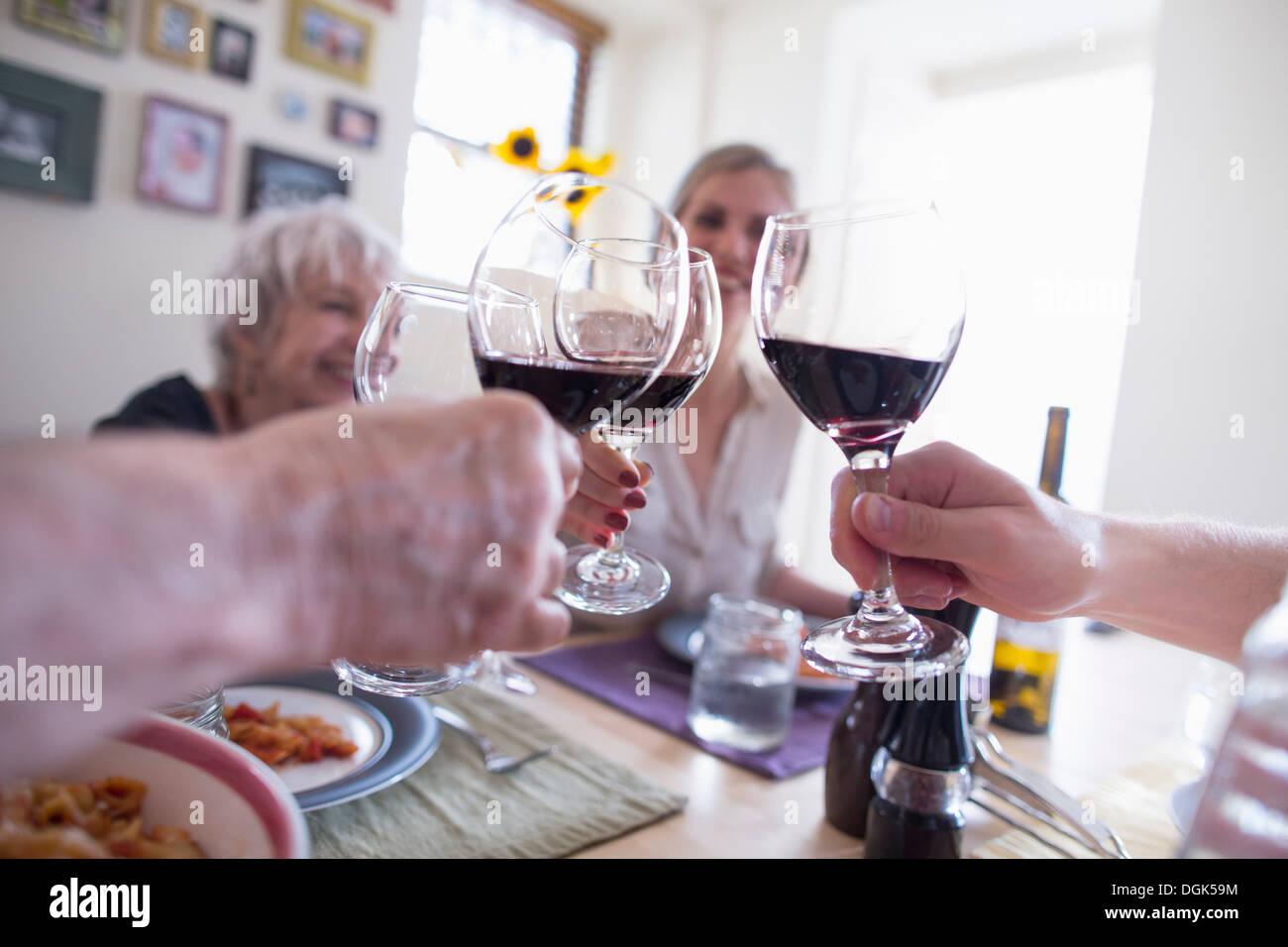 Tostatura di famiglia con un bicchiere di vino rosso a cena Immagini Stock