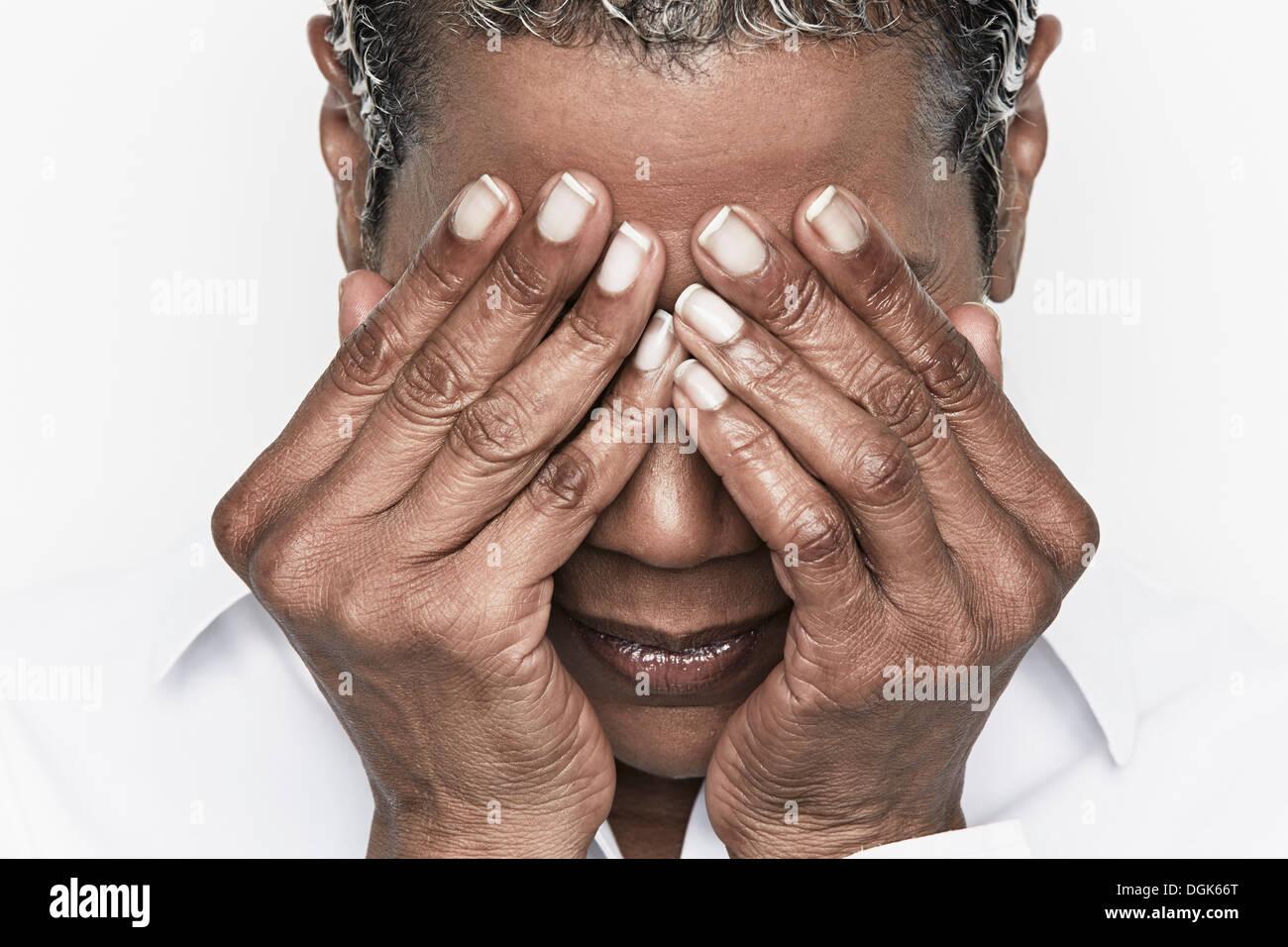 Senior donna che copre i suoi occhi Immagini Stock