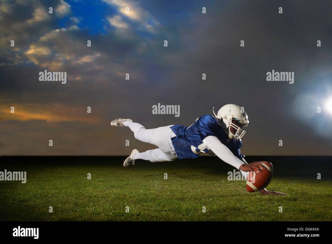 Giocatore di football americano raggiungendo per touch down Immagini Stock