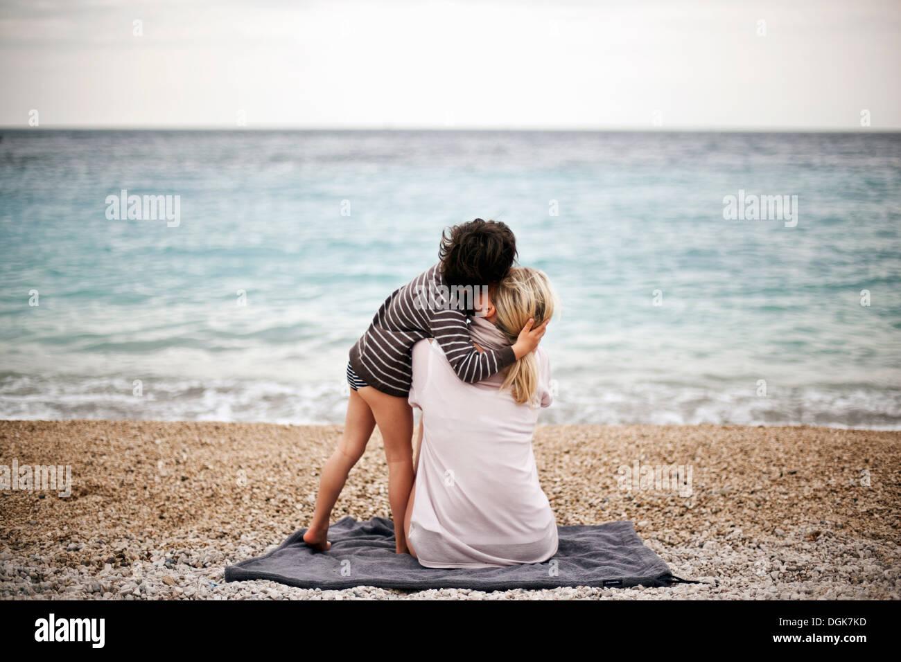 Ragazzo abbracciando la madre su una spiaggia, vista posteriore Foto Stock