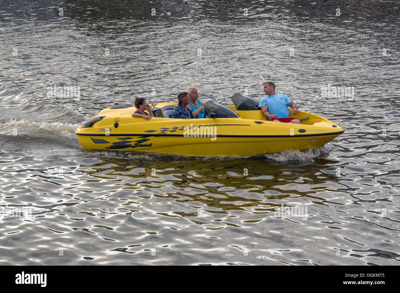 Persone coppie crociera in un piccolo, giallo motore entrobordo speedboat. Estate Tempo libero vacanza di ricreazione. Immagini Stock