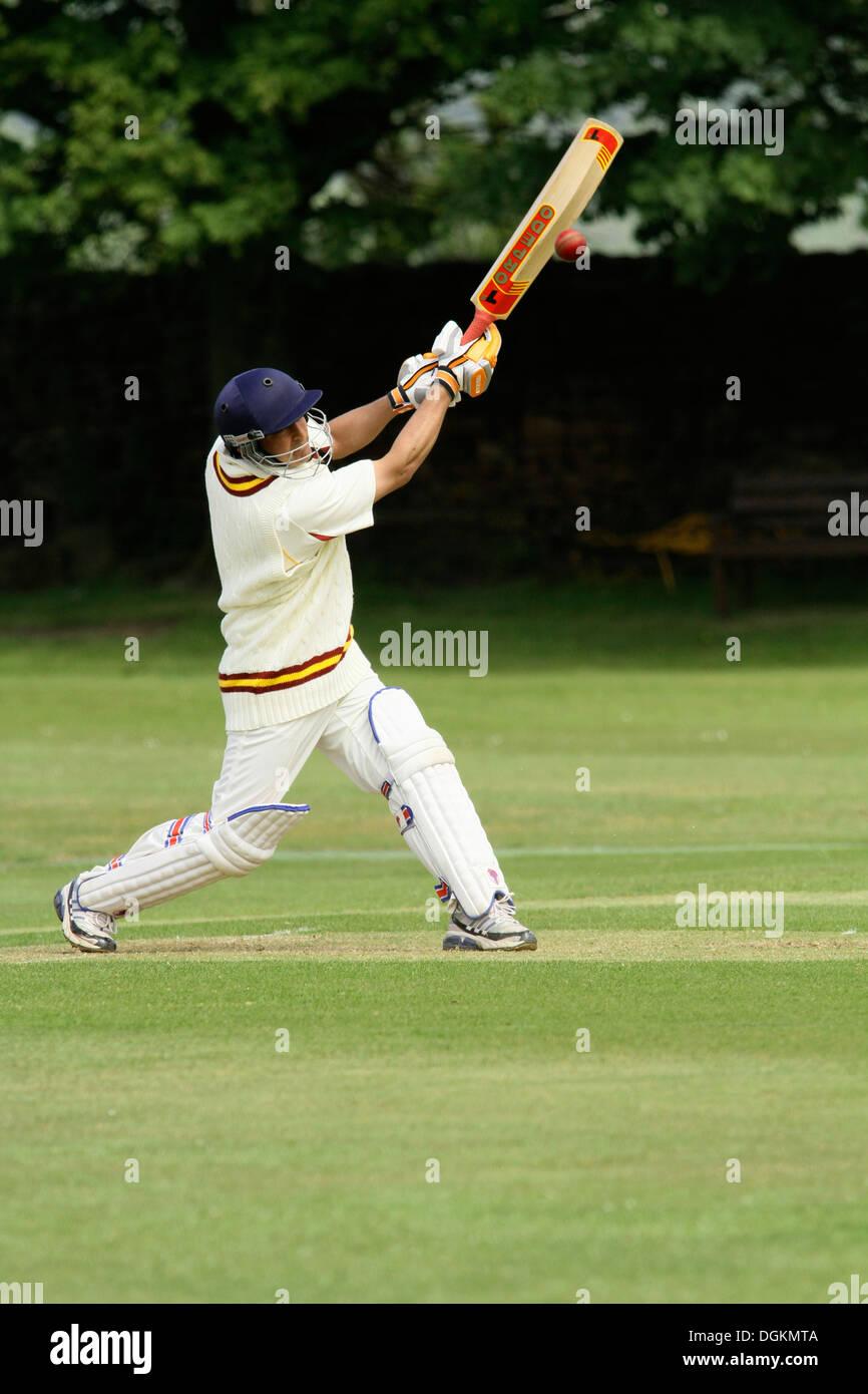 Un cricketer in pieno gli indumenti di protezione la guida la palla verso il visualizzatore. Immagini Stock