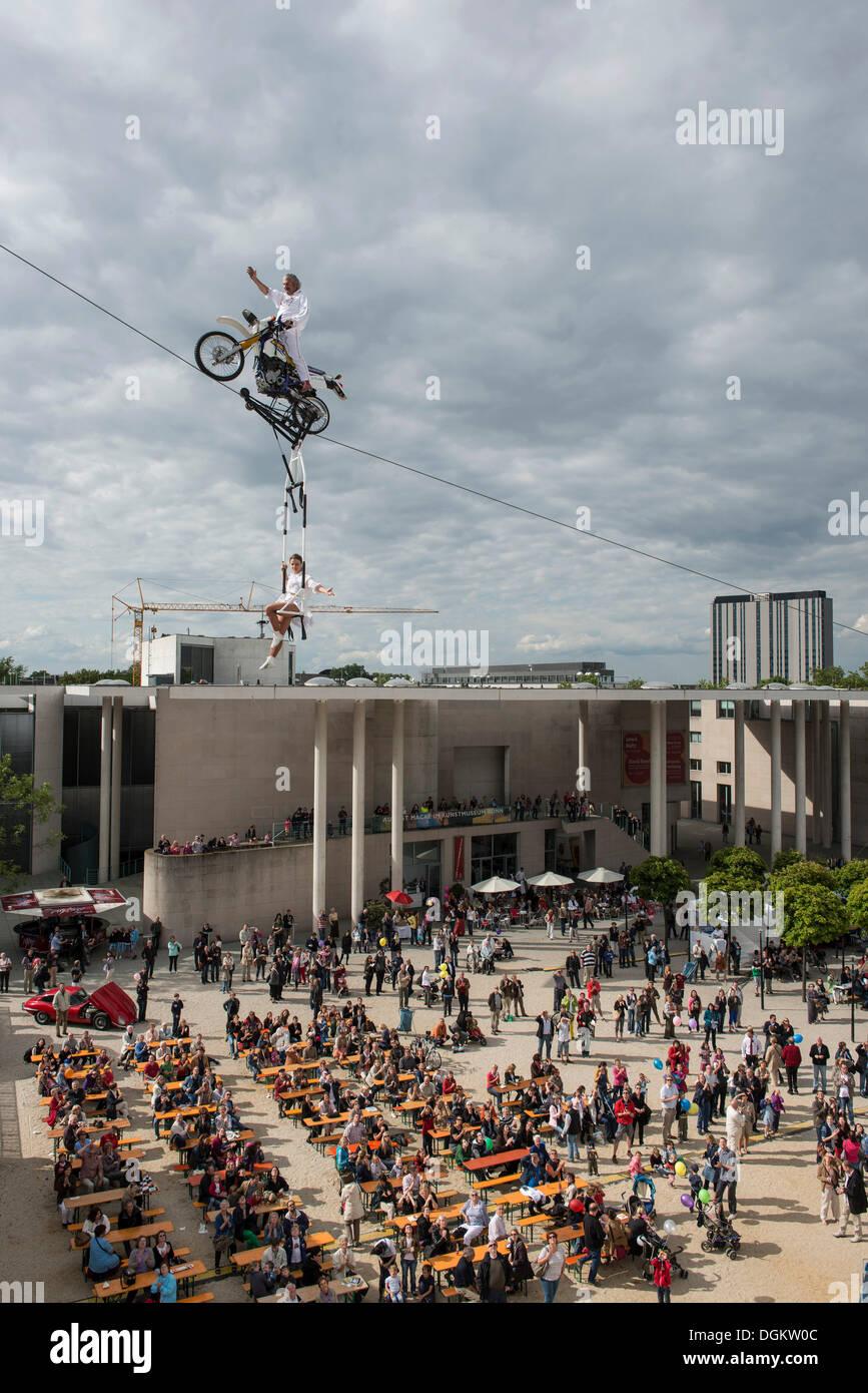 Museum Mile Festival, ad alta filo artista Falko Traber in sella a una motocicletta sulla fune, udienza al di sotto, Bonn Immagini Stock