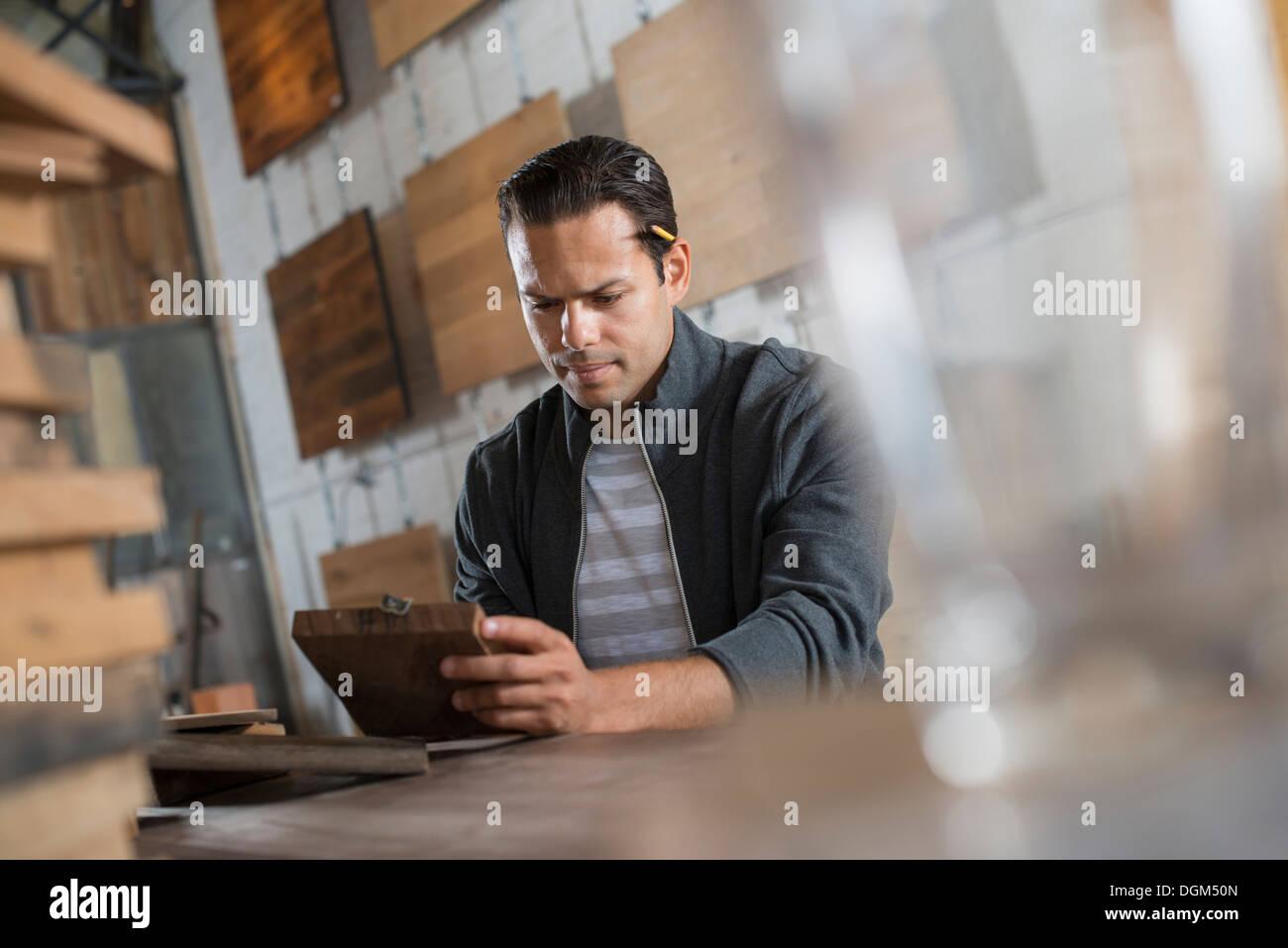 Un giovane uomo in un laboratorio che utilizza materiali riciclati e rigenerati legname a creare mobili e oggetti. Immagini Stock