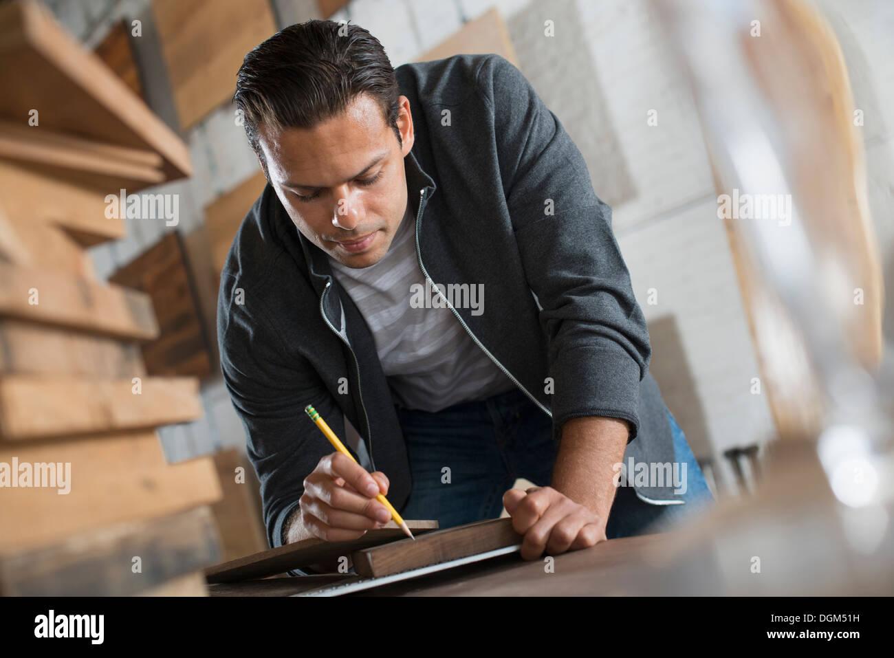 Un giovane uomo in un laboratorio che utilizza materiali riciclati e rigenerati legname utilizzando carta e penna per conservare i record. Immagini Stock