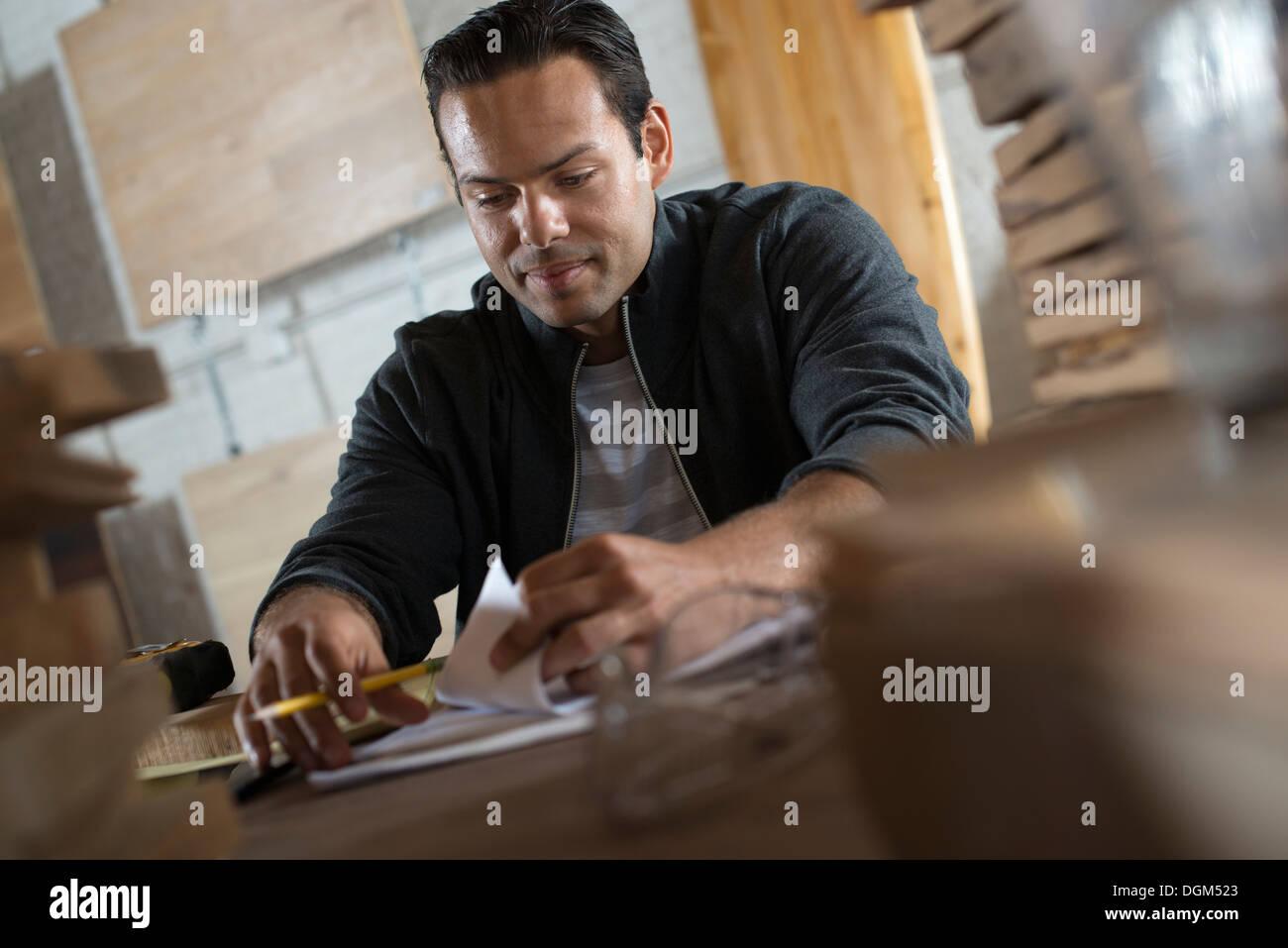 Un giovane uomo in un workshop usando carta e penna per conservare i record. Immagini Stock