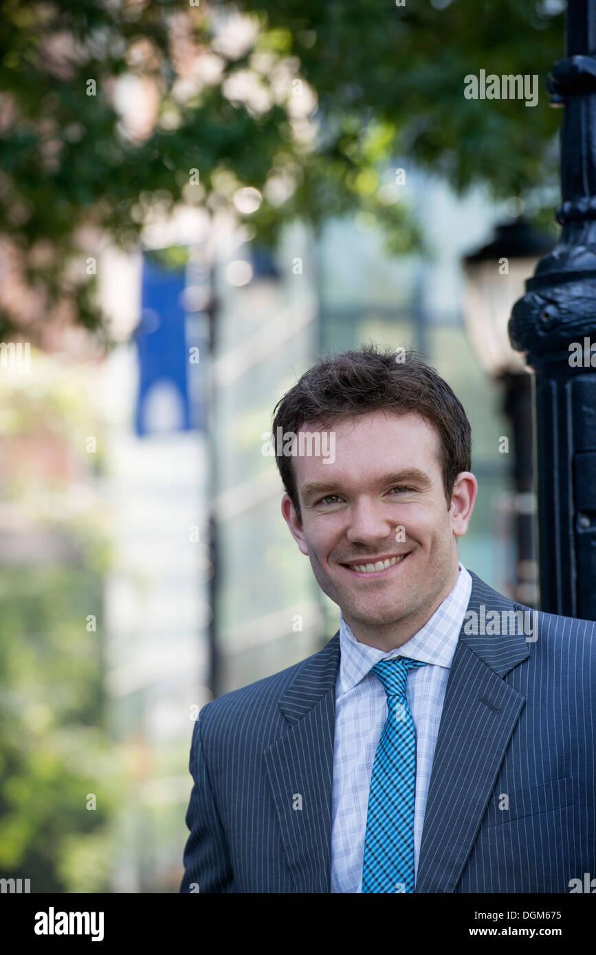 L'estate. Un giovane uomo in un completo grigio e cravatta blu. Immagini Stock
