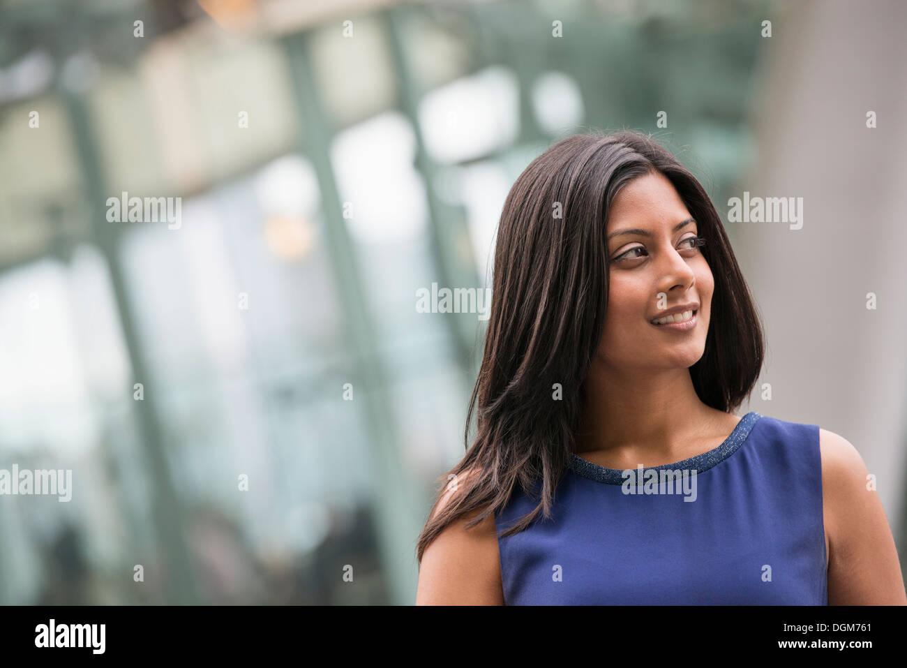 La gente di affari. Una donna con lunghi capelli neri che indossa un vestito blu. Foto Stock