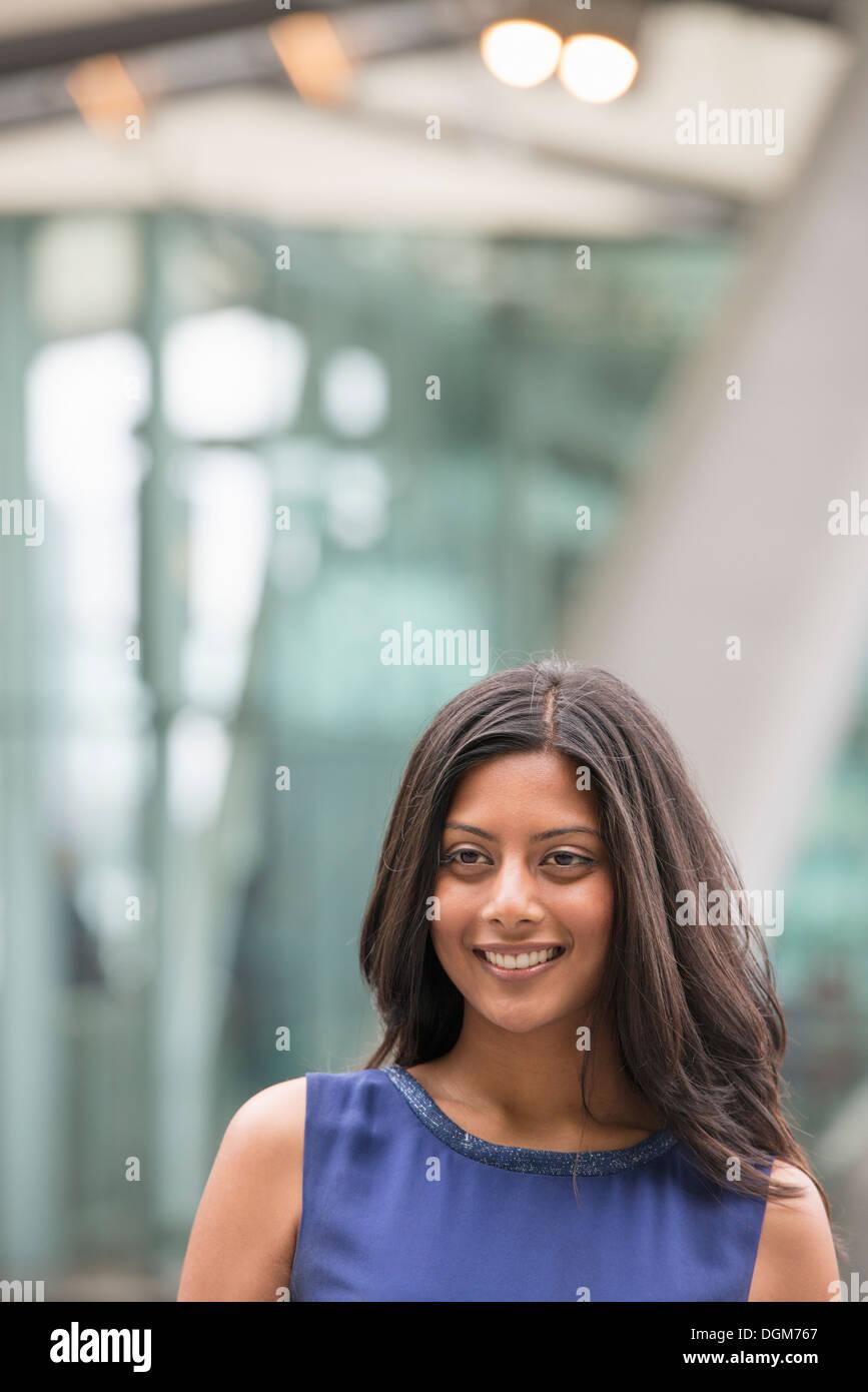 La gente di affari. Una donna con lunghi capelli neri che indossa un vestito blu. Immagini Stock