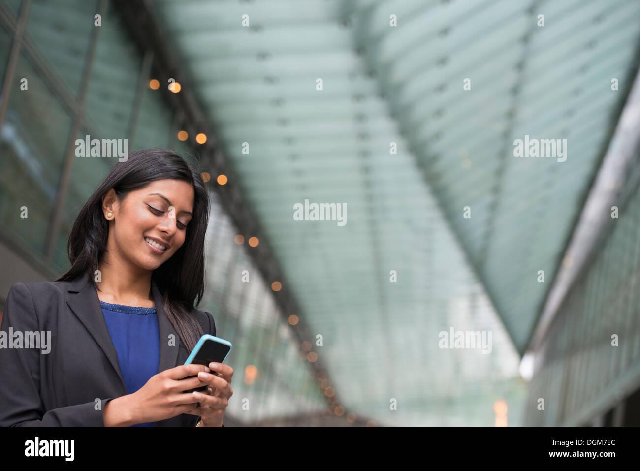 La gente di affari. Una giovane donna in un vestito blu e giacca grigia. Immagini Stock