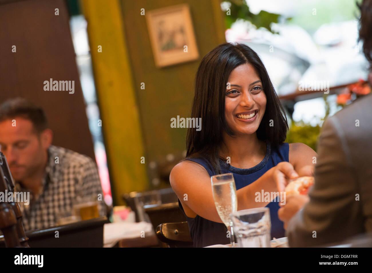 La gente di affari. Due persone sedute a un tavolo tenendo le mani. Un uomo in background. Immagini Stock